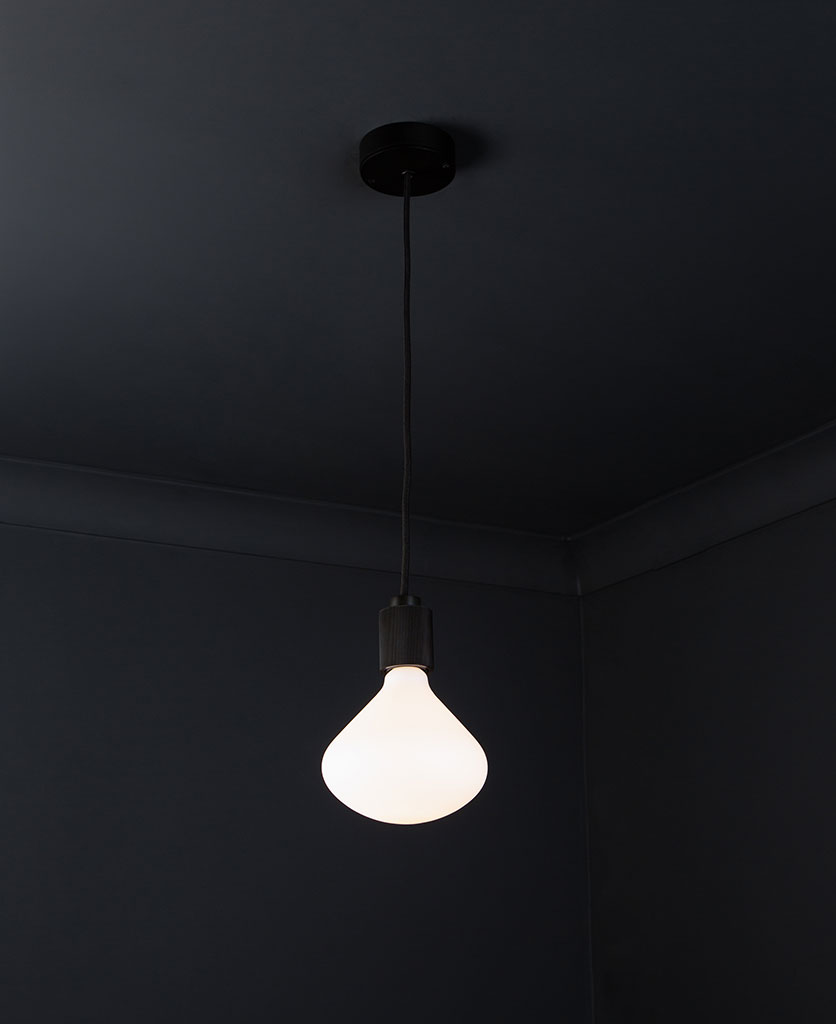black lanesborough pendant ceiling light suspended from a black ceiling rose with black fabric cable and opal light bulb against a black wall