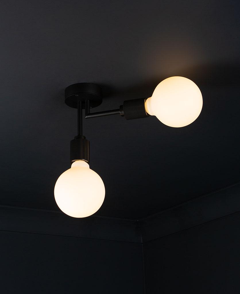 Langham LED flush ceiling lights black two arm light with 2 lit bulbs against a black background