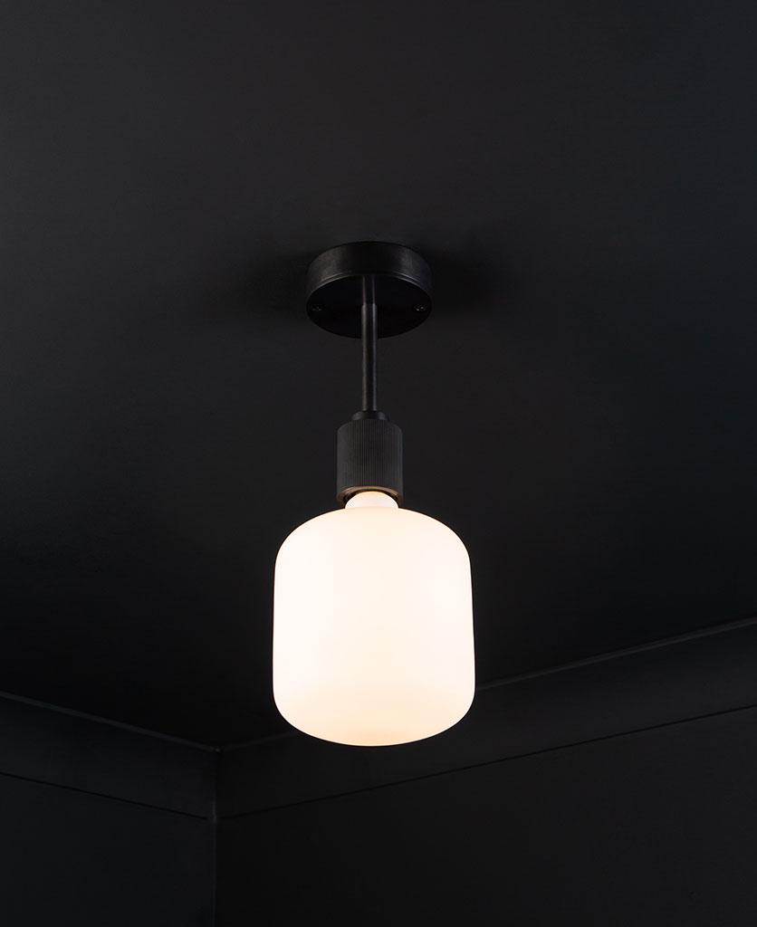 black Portobello flush mount ceiling light with lit light bulb on black ceiling