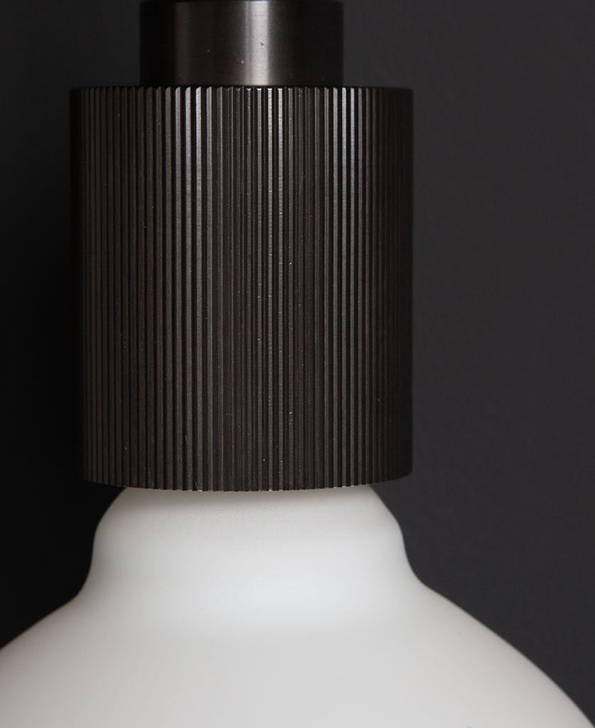 black ribbed bulb holder against black wall