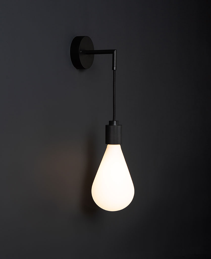 ritz black wall light fittings with lit bulb against black background