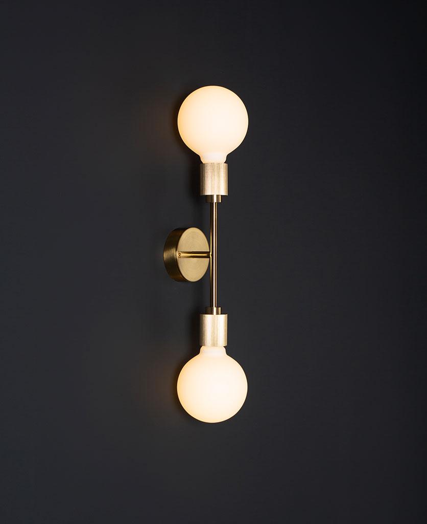 belgravia brass lit LED wall light against black wall