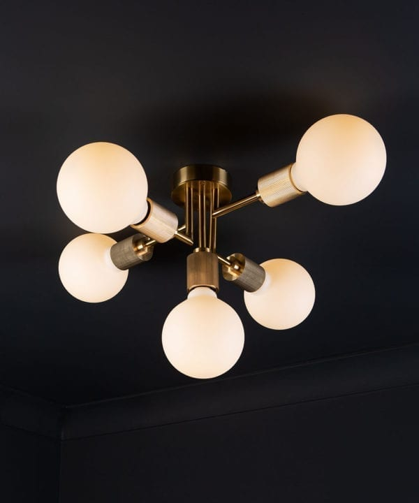 connaught flush ceiling light gold ceiling light with 5 bulbs on black ceiling.
