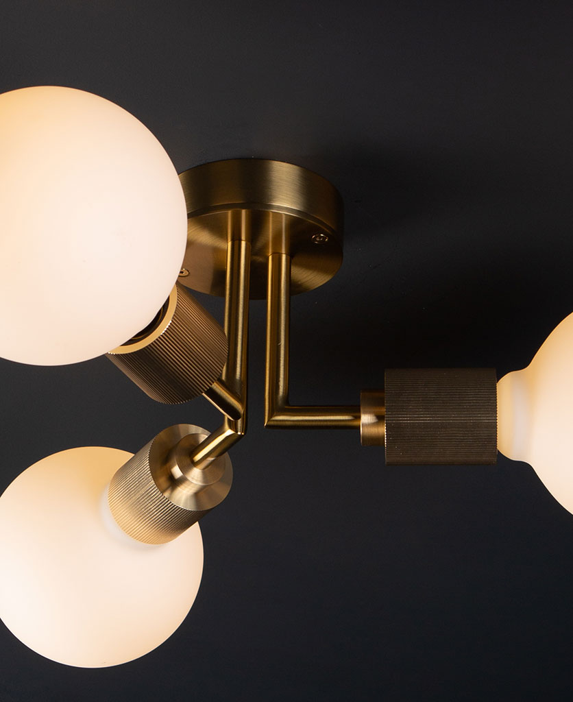 closeup hoxton gold ceiling light with 3 lit bulbs on black ceiling