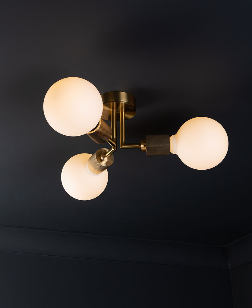 semi flush ceiling lights hoxton gold ceiling light with 3 lit bulbs on black ceiling