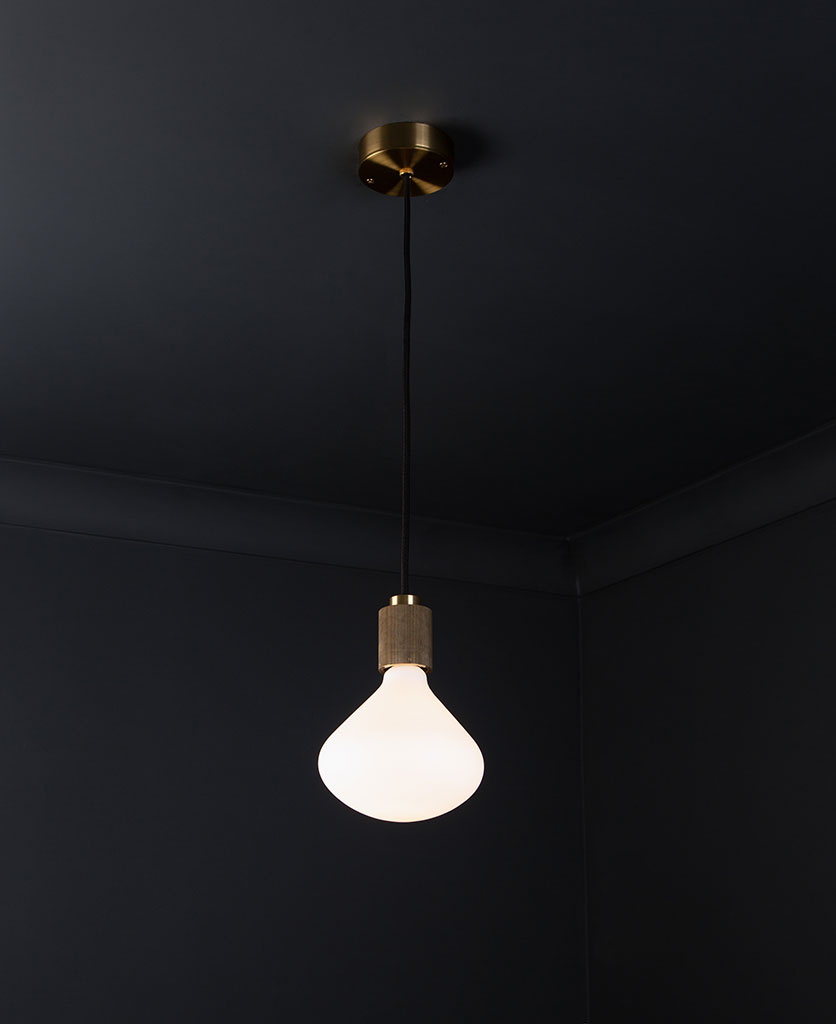 gold lanesborough pendant ceiling light suspended from a gold ceiling rose with black fabric cable and opal light bulb against a black wall