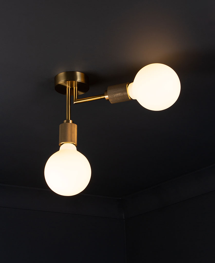 Langham LED flush ceiling lights gold two arm light with 2 lit bulbs against a black background