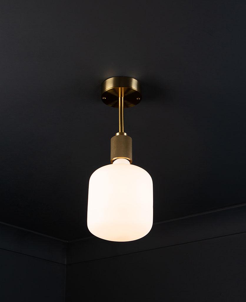 gold Portobello flush mount ceiling light with lit light bulb on black ceiling
