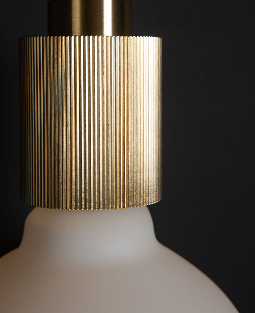brass ribbed bulb holder against black wall