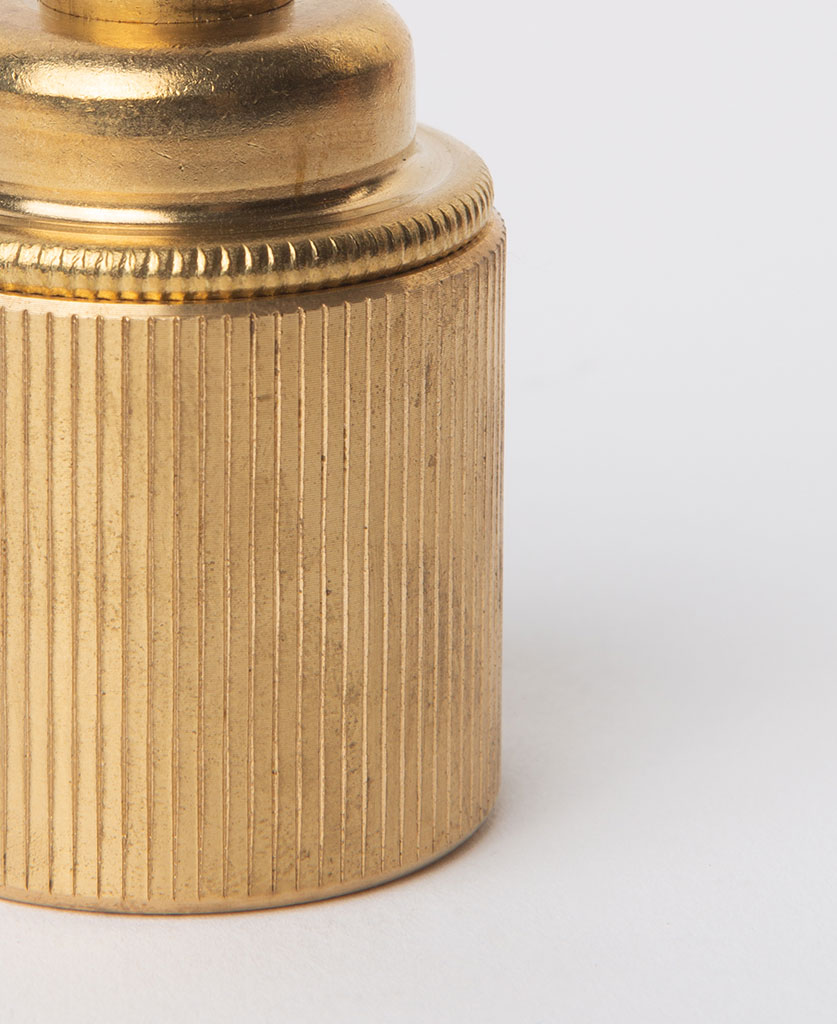 closeup of e27 raw brass lamp holderwith ribbed detail against white background