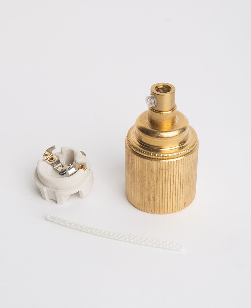 e27 raw brass lamp holderwith ribbed detail with porcelain insert against white background