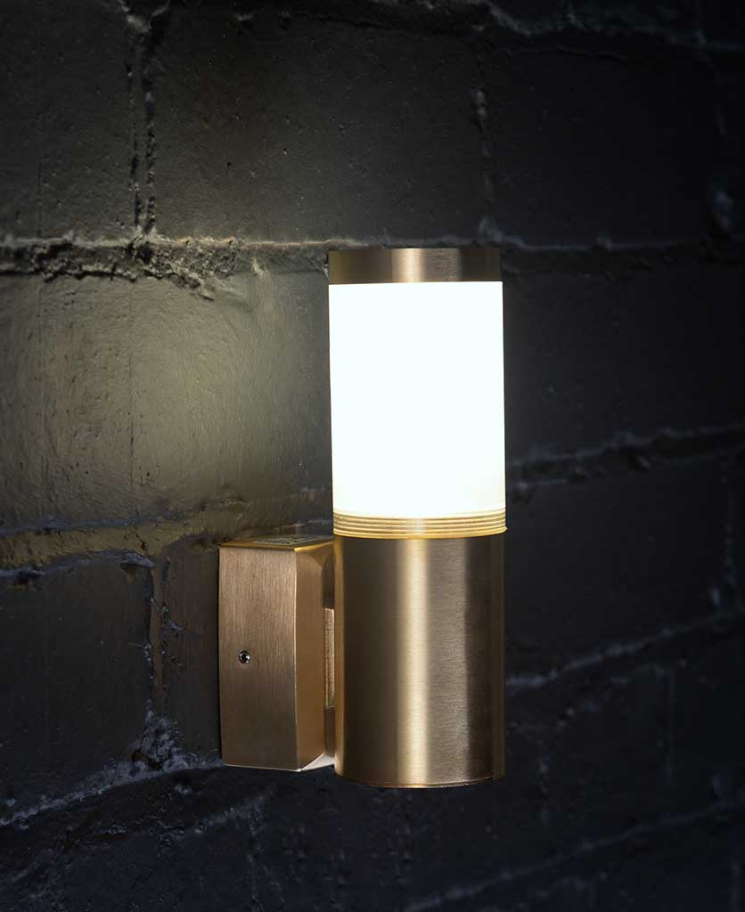 outside wall light gliese brass on black painted brick wall