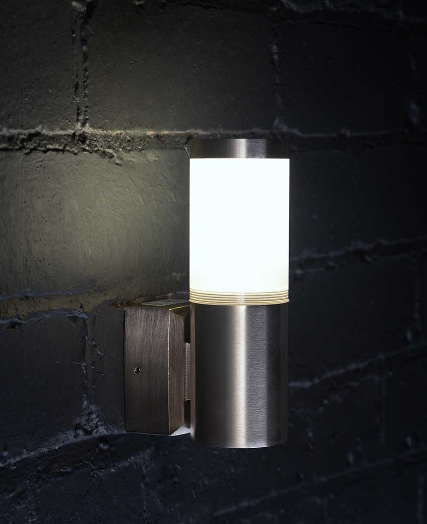 gliese tin silver wall light on black painted brick wall