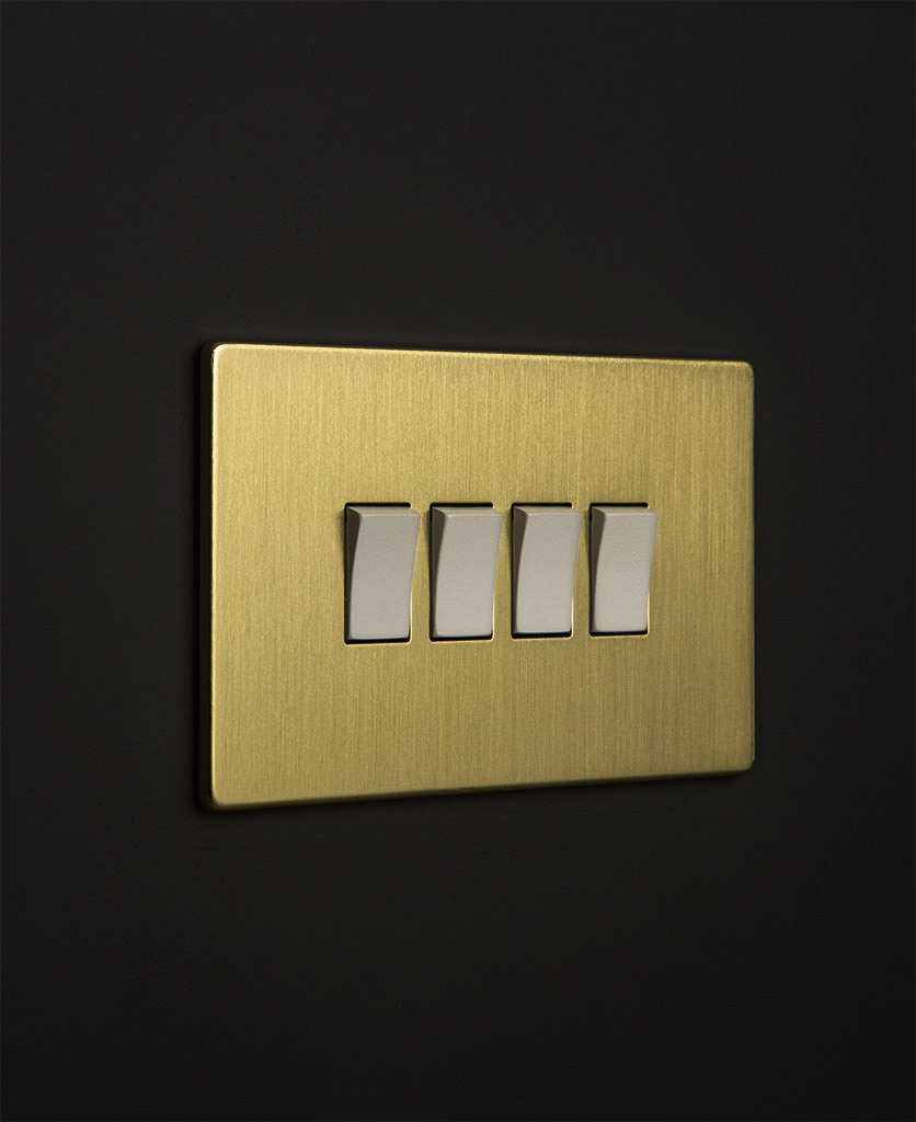 gold 4 gang switch with white rocker detail on a black wall