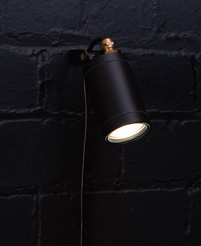 black leonis wall light against black painted brick wall