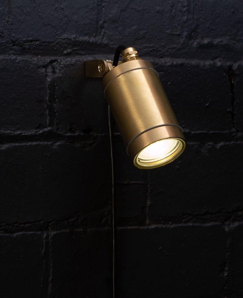leonis raw brass against black brick wall