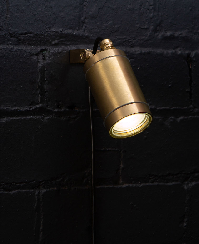 brass leonis wall light against black painted brick wall