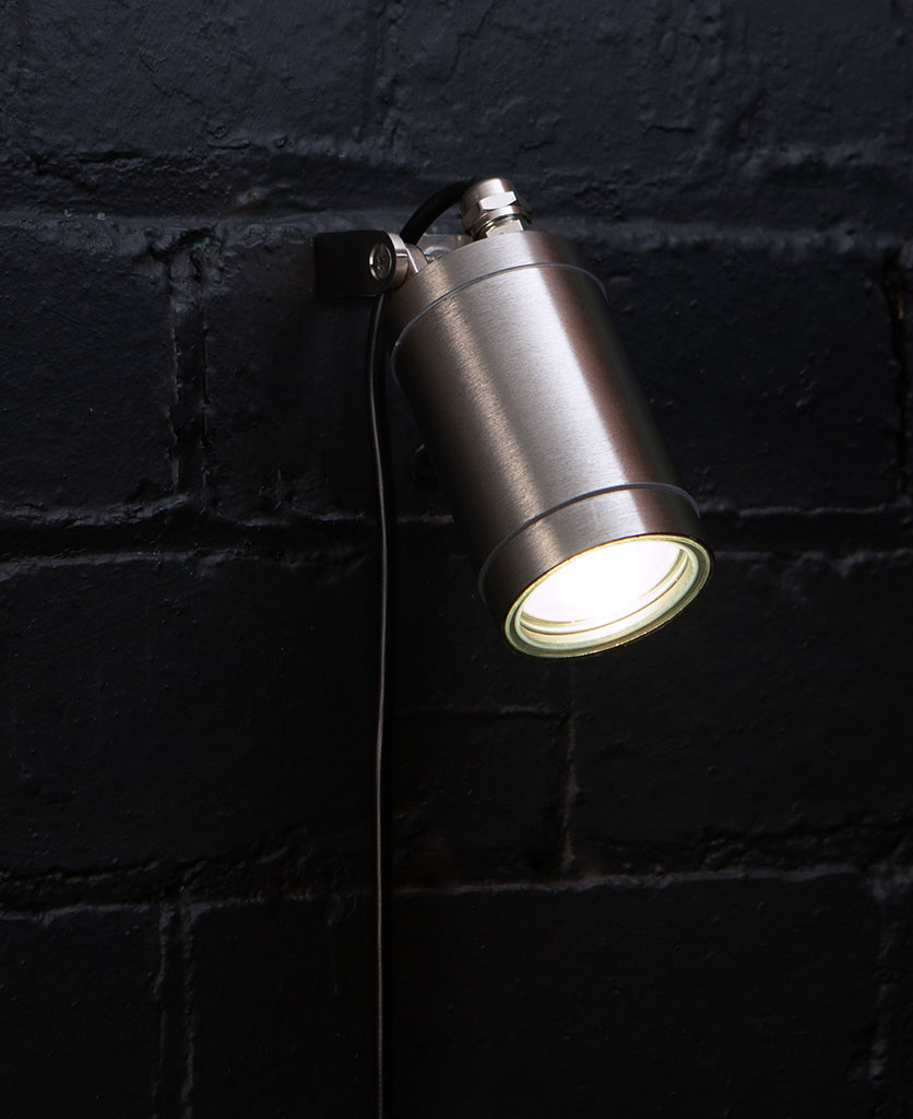 silver leonis wall light against black painted brick wall