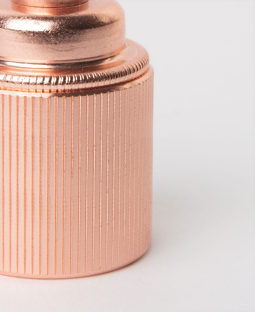 closeup of polished copper e27 ribbed screw lamp holder against white background