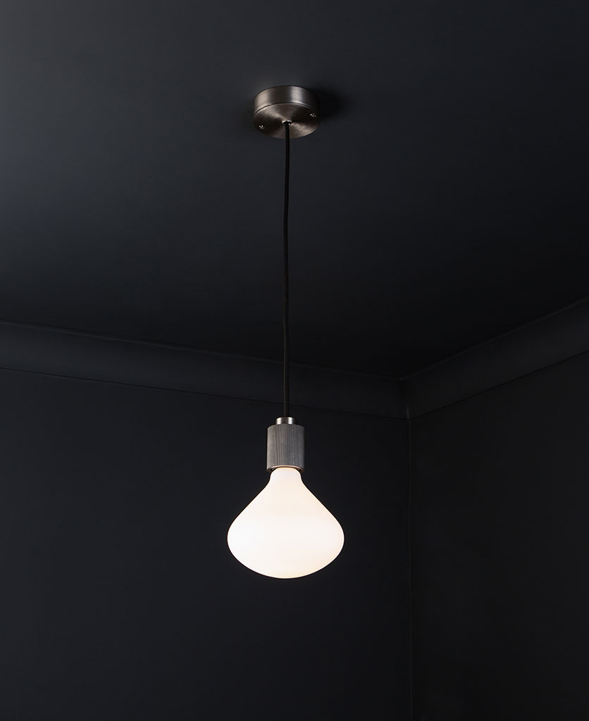silver lanesborough pendant ceiling light suspended from a silver ceiling rose with black fabric cable and opal light bulb against a black wall