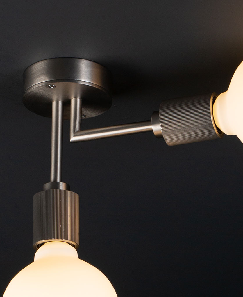 closeup of Langham LED flush ceiling lights silver two arm light with 2 lit bulbs against a black background