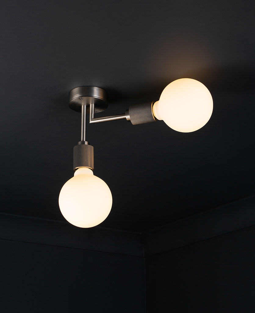 Langham LED flush ceiling lights silver two arm light with 2 lit bulbs against a black background