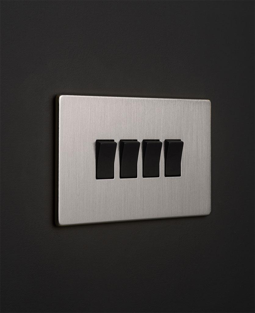 silver 4g switcher with quadruple black rocker detail on a black wall