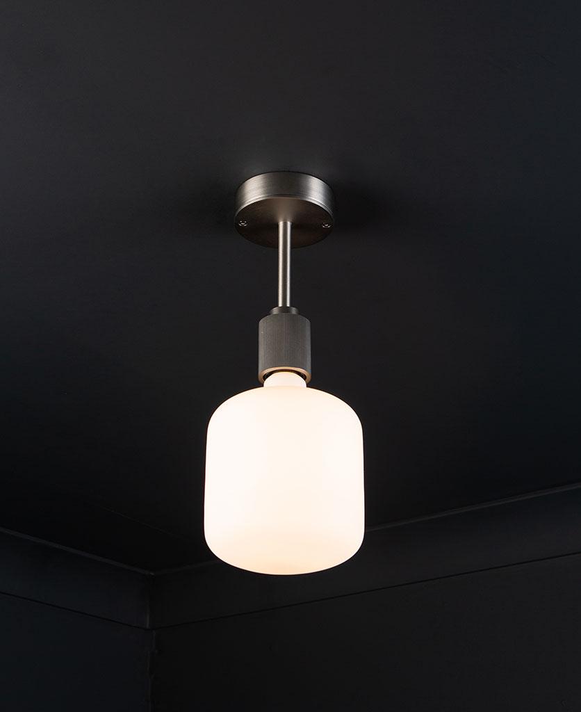 silver Portobello flush mount ceiling light with lit light bulb on black ceiling