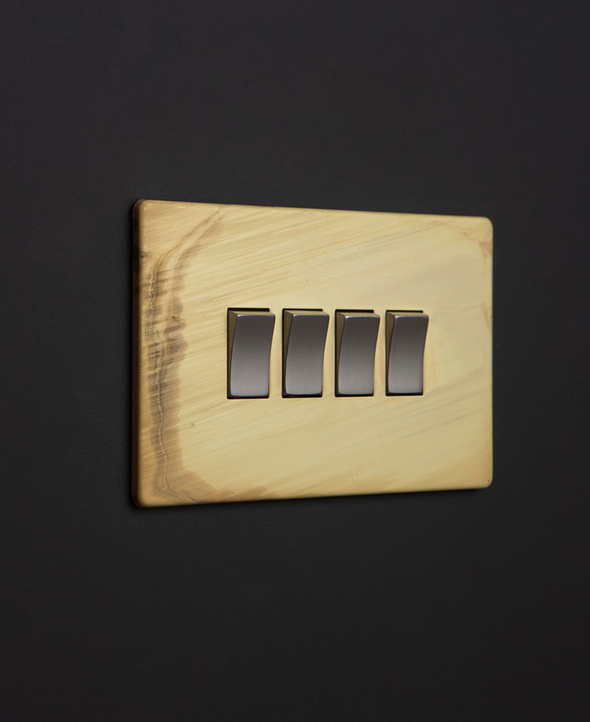 smoked gold on off rocker switch with silver rocker detailing on black wall