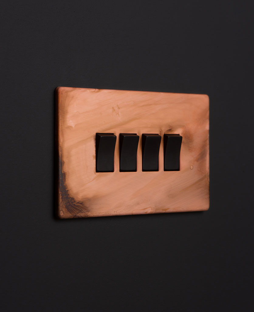 Copper light switches with quad black rocker detail on a black wall