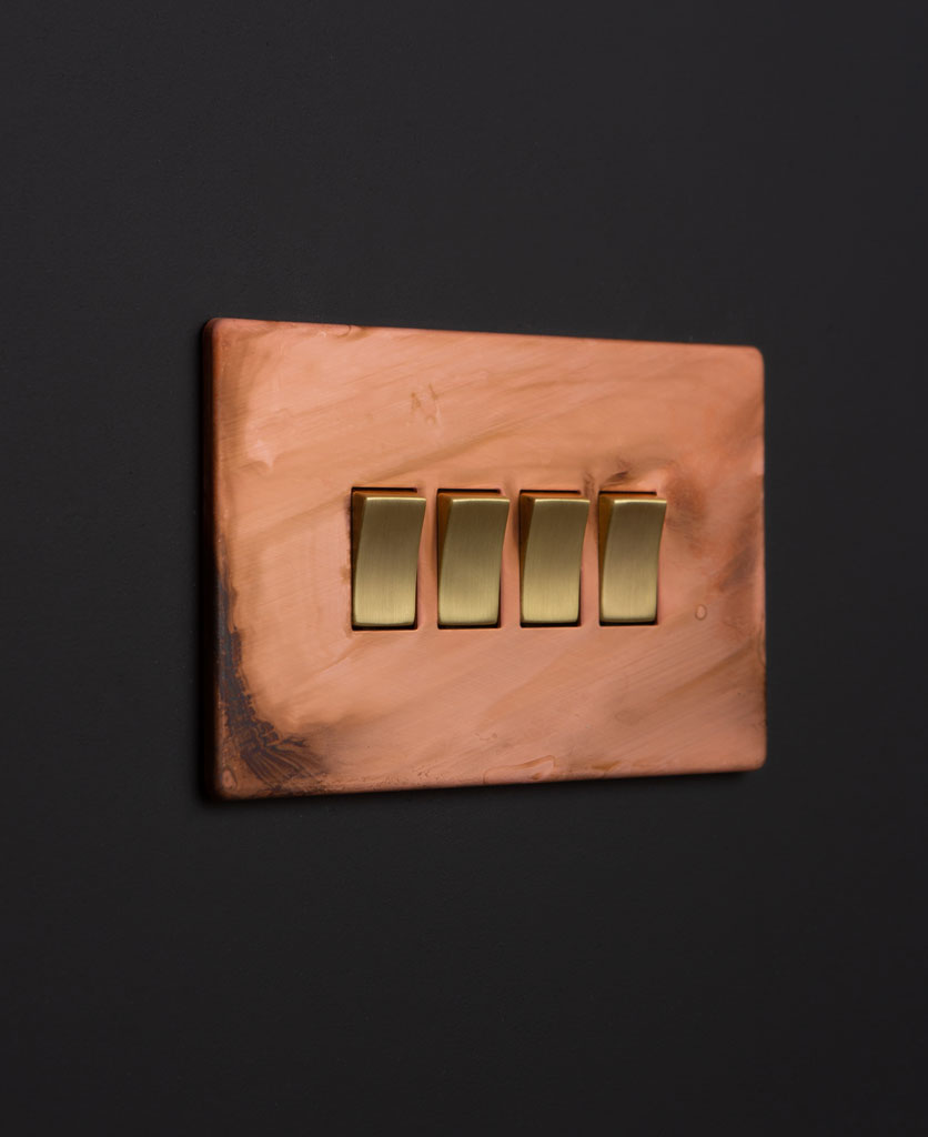 Copper light switches with quad gold rocker detail on a black wall