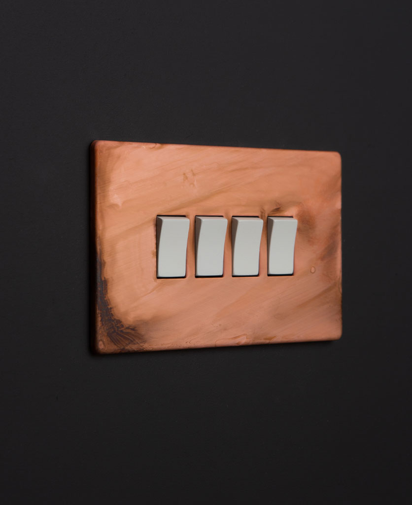 Copper light switches with quad white rocker detail on a black wall