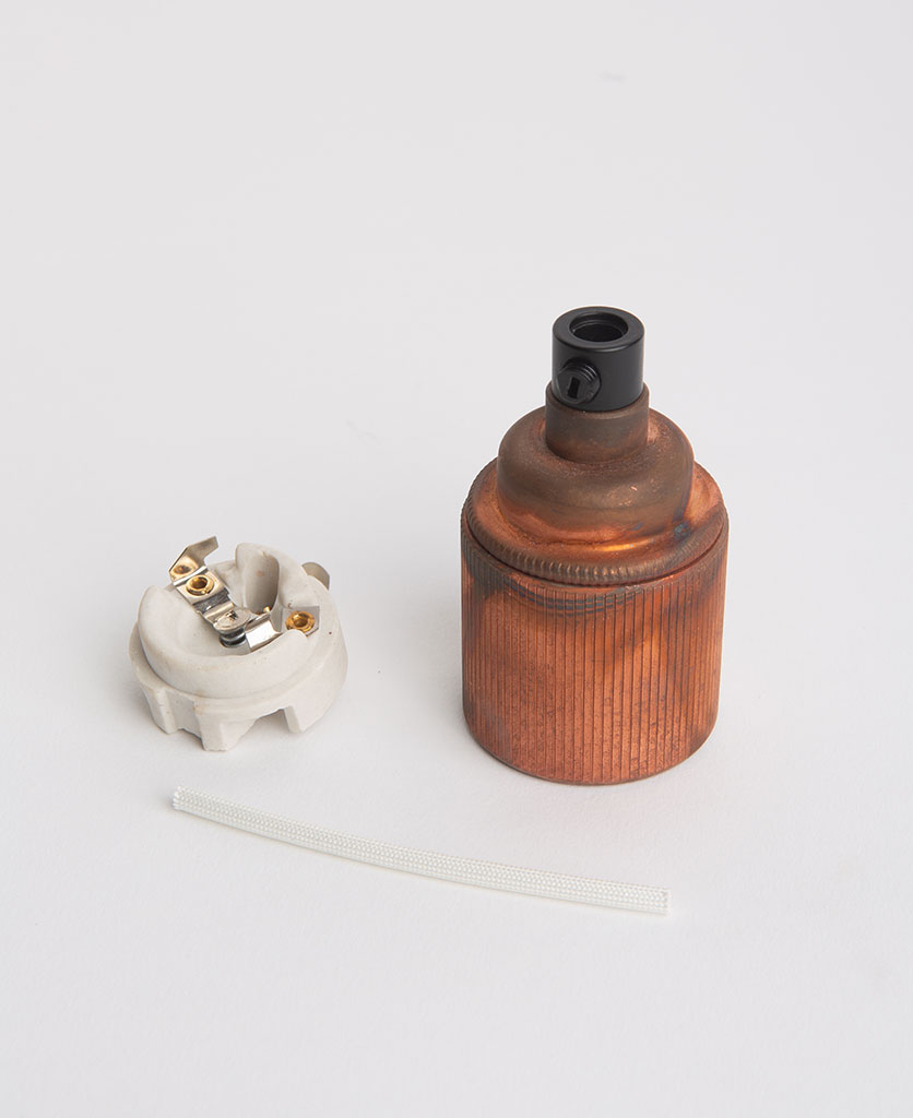 tarnished copper edison screw lamp holder with porcelain inserts against white background