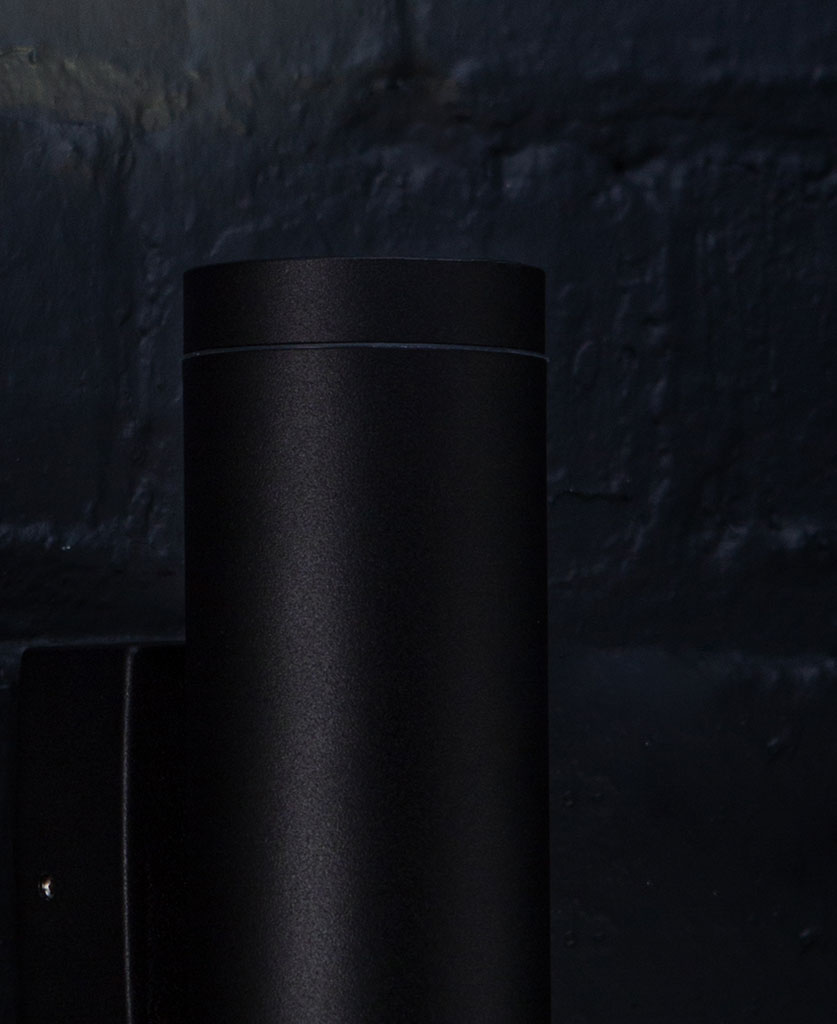 closeup of vega black wall light on black painted brick wall