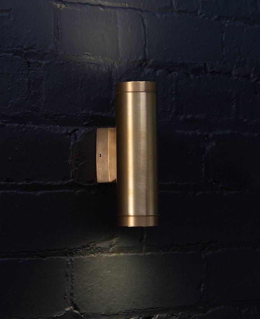 vega raw brass against black painted brick wall