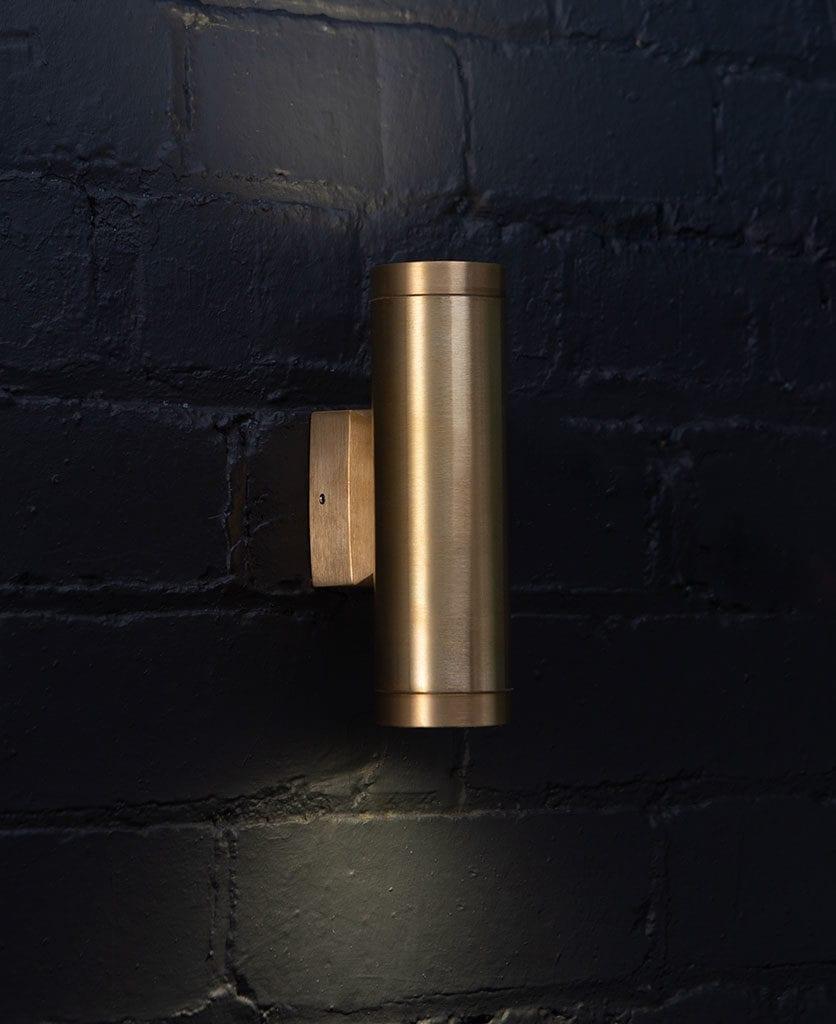 Vega Brass Outdoor Wall Light on black painted brick wall