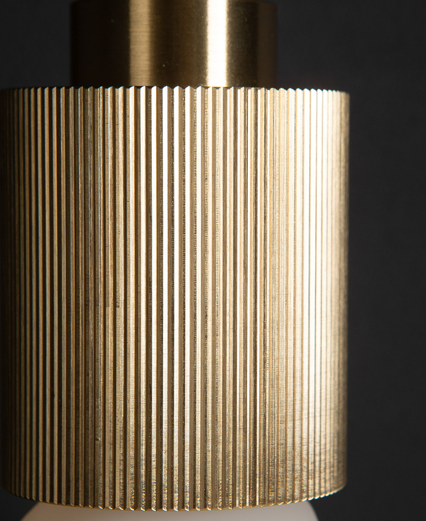 raw brass ribbed bulb holder closeup against black background