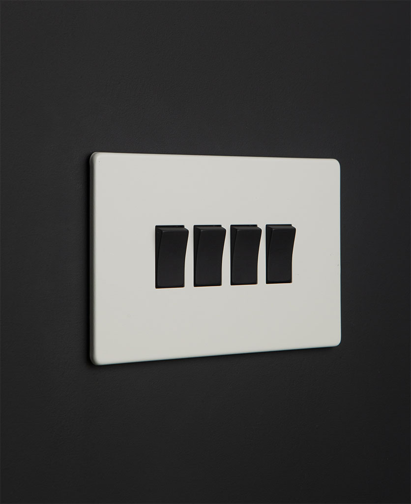 white 4 gang light switch with black rocker detailing on a black wall