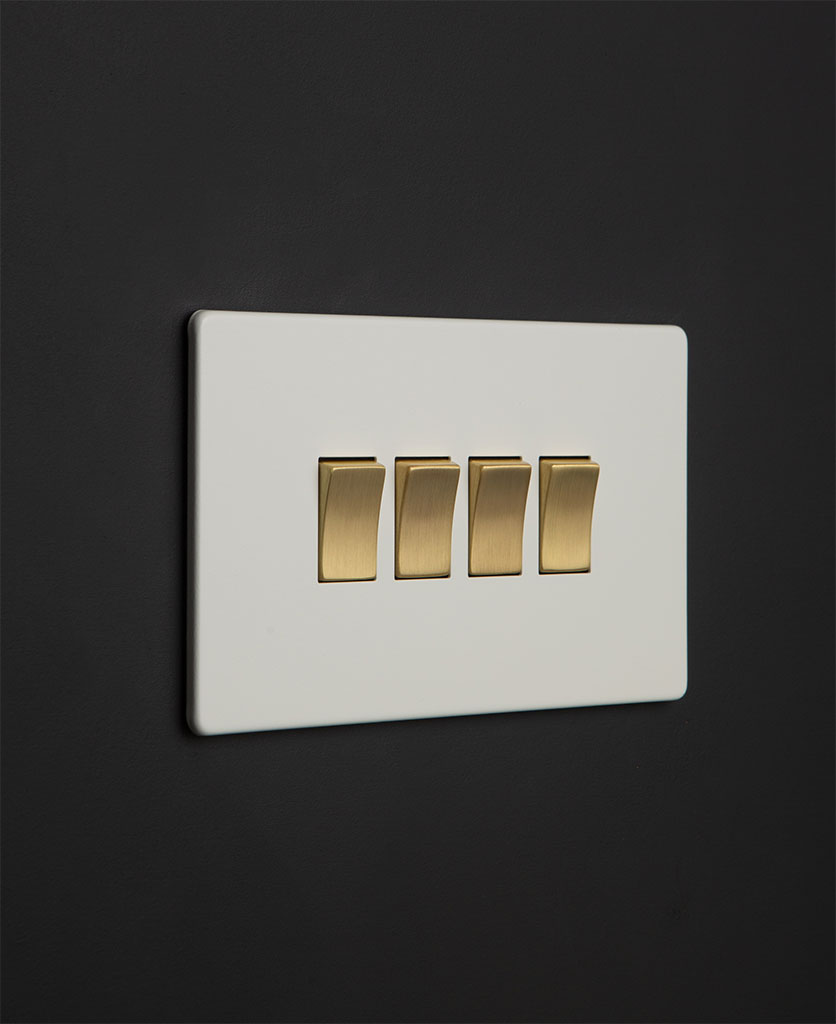 white 4 gang light switch with gold rocker detailing on a black wall