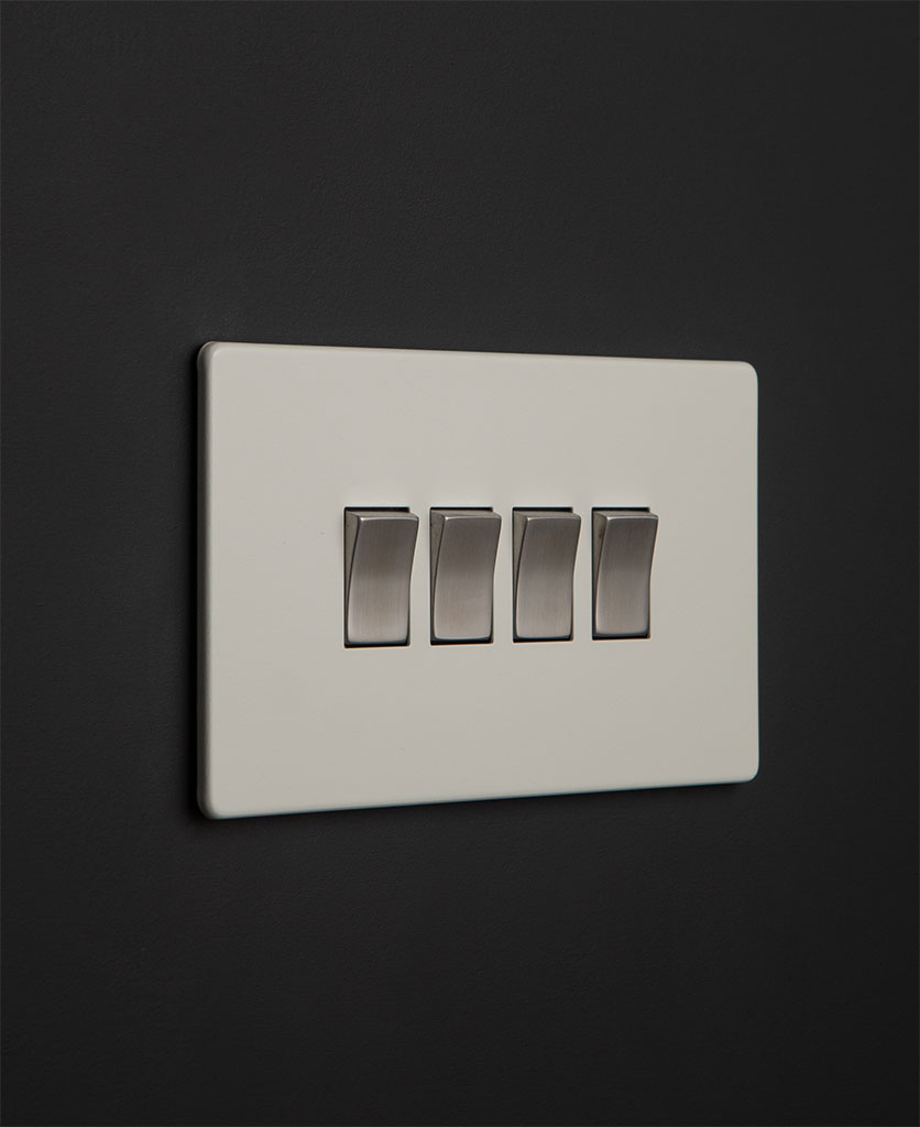 white 4 gang light switch with silver rocker detailing on a black wall