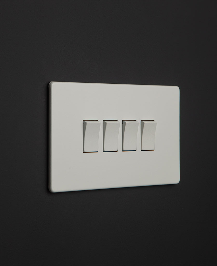 white 4 gang light switch with white rocker detailing on a black wall