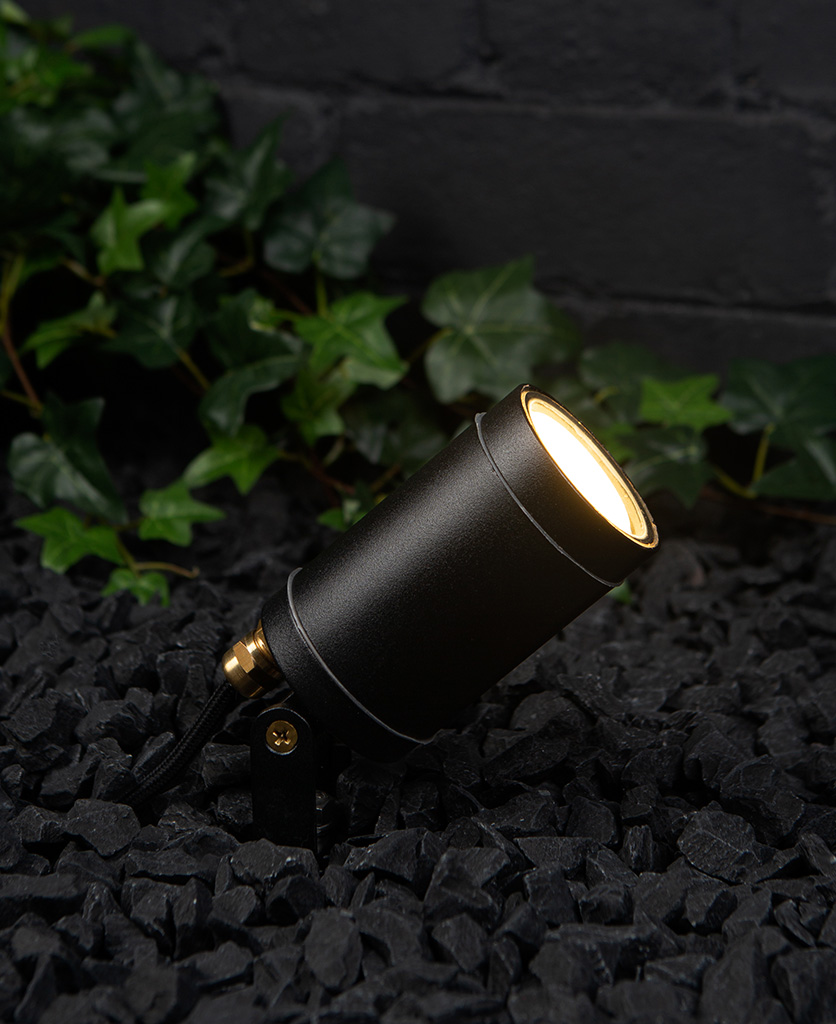 zosma black led spike light in black gravel against a black painted brick wall