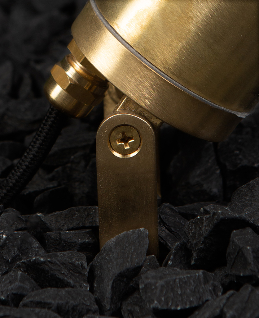 closeup of zosma brass outside light in black gravel against black painted brick wall
