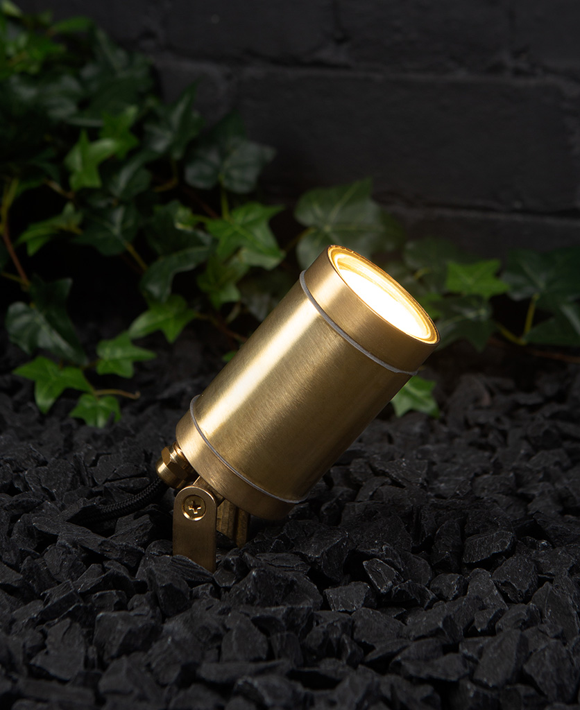 zosma brass outside light in black gravel against black painted brick wall