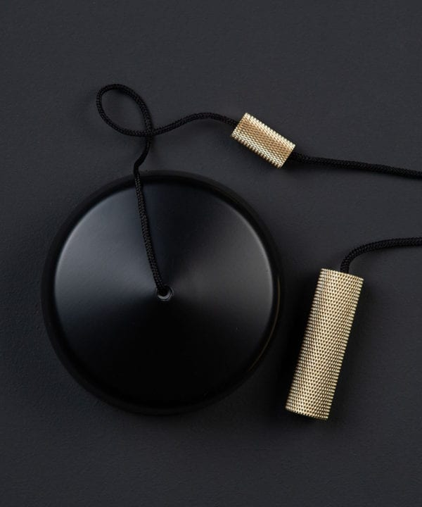 black pull cord switch with brass pull against black background