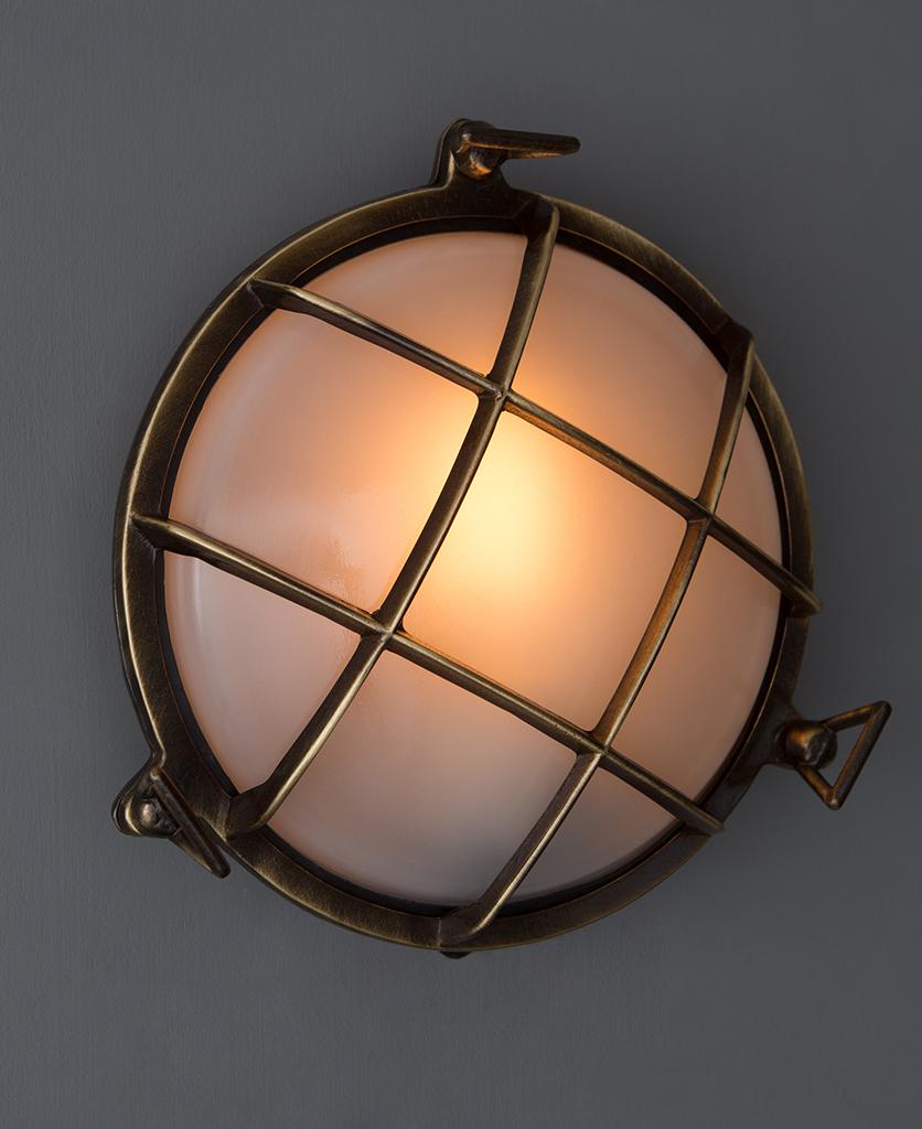 lit chris aged brass bulkhead led light against grey wall