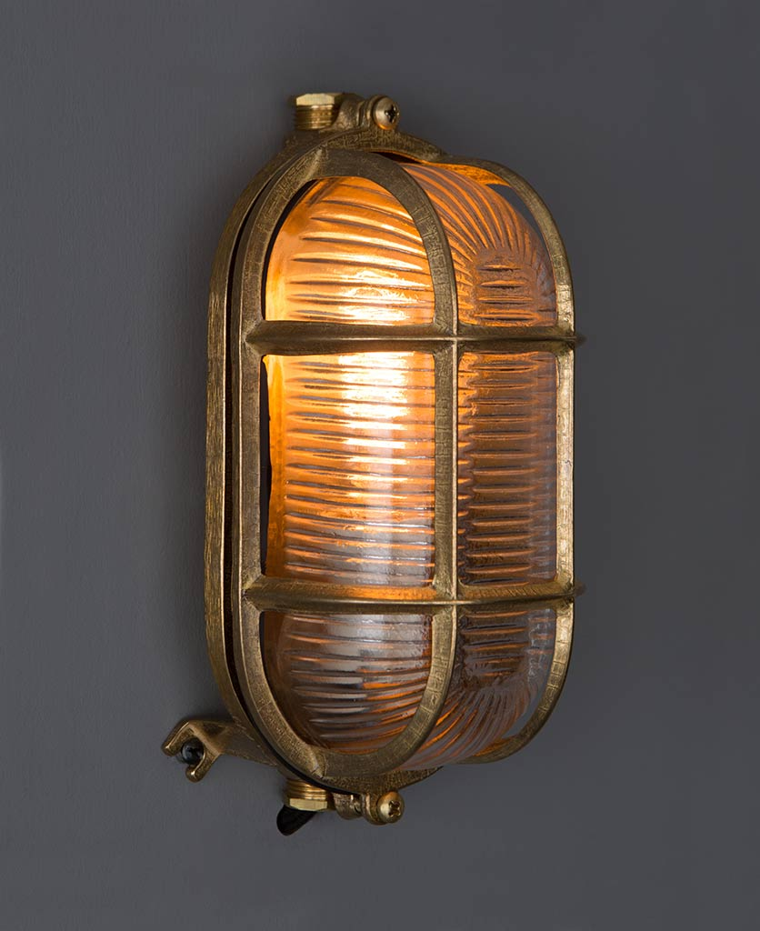 lit outdoor bulkhead light dave brass against grey background