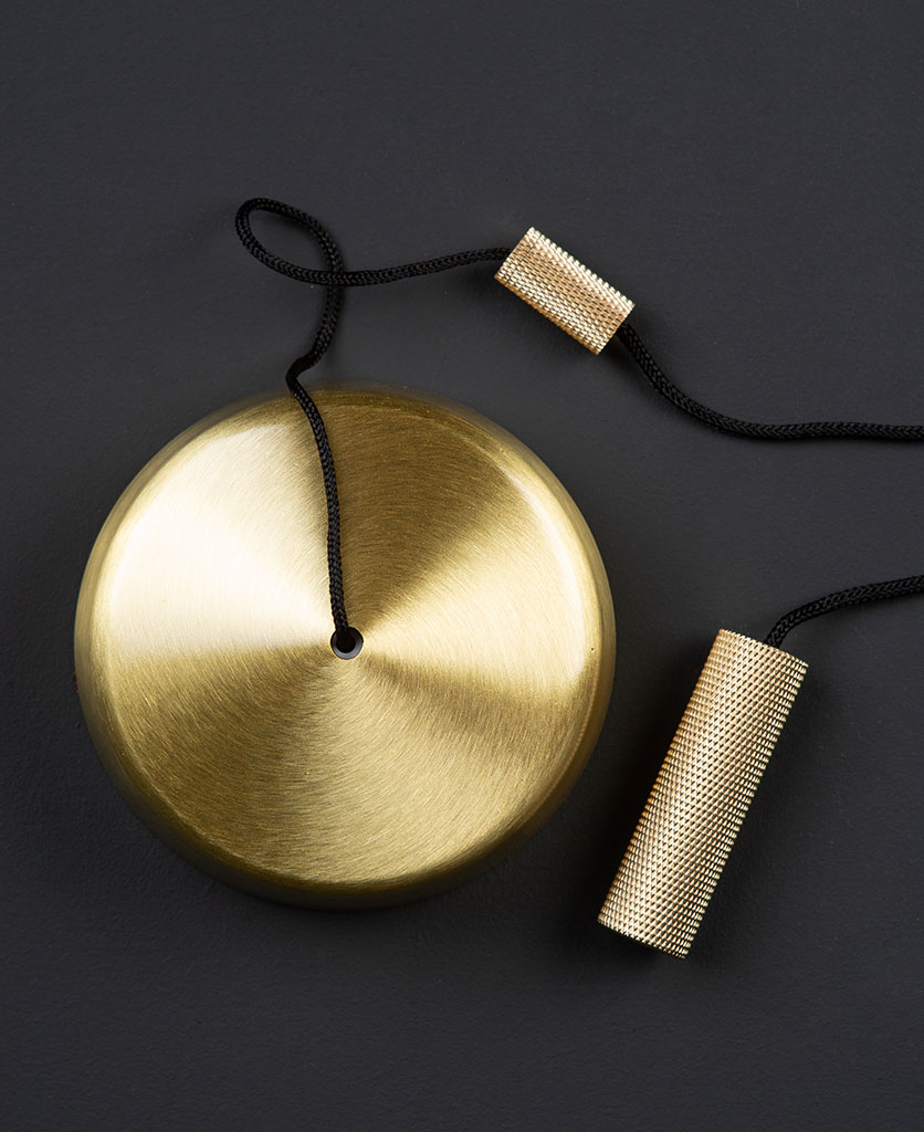 brass pull cord switch with brass pull against black background