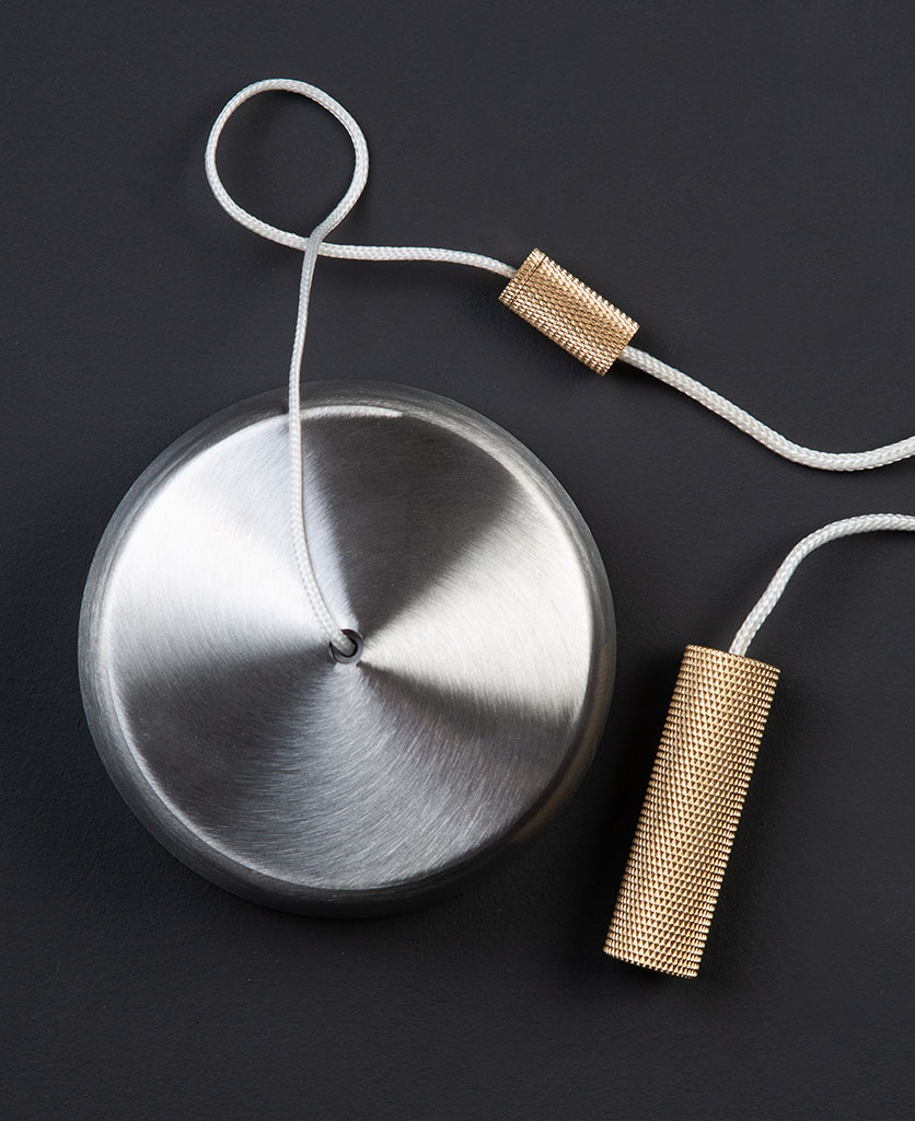 silver pull cord switch with brass pull against black background
