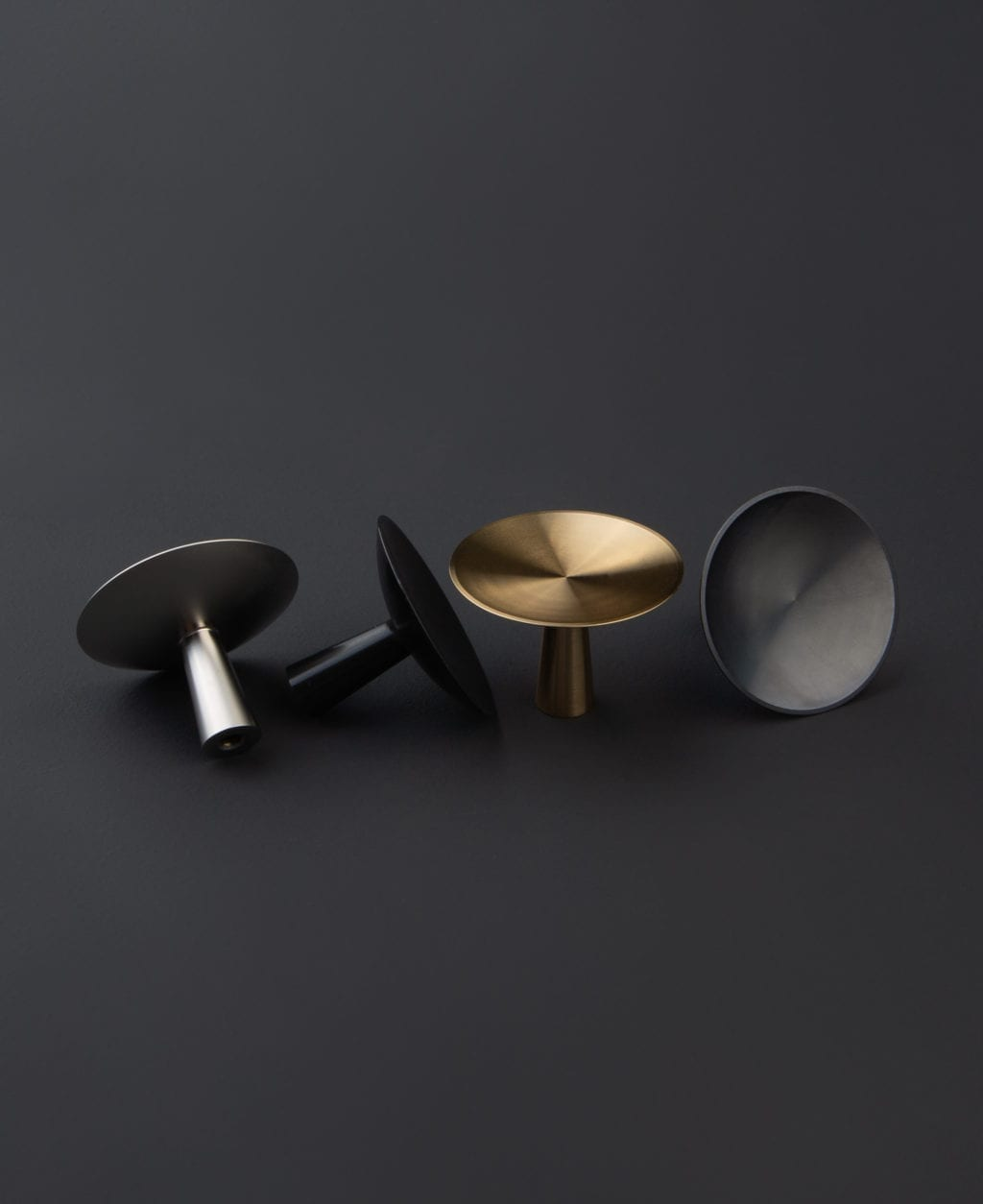 group shot of four rococo kitchen knobs in silver, black, gold and antique black against black background